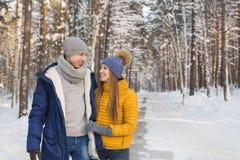 Pares jovenes sonrientes que parecen cara a cara en un bosque en el invierno Foto de archivo libre de regalías