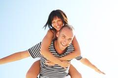 Pares jovenes sonrientes que se divierten en la playa Foto de archivo libre de regalías