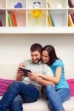 Junte sentarse en el sofá y la mirada de la PC de la tableta Imagen de archivo libre de regalías