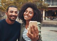 Pares jovenes sonrientes que toman el selfie en el teléfono elegante foto de archivo libre de regalías