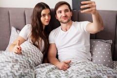 Pares jovenes sonrientes que toman el selfie junto en dormitorio imagen de archivo