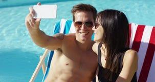 Pares jovenes sonrientes que toman un selfie de las vacaciones almacen de video