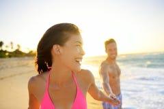 Pares jovenes sonrientes románticos en la playa en puesta del sol Imagenes de archivo