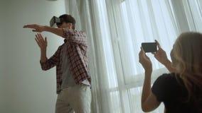 Pares jovenes sonrientes usando las auriculares de Vr en casa almacen de metraje de vídeo