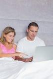 Pares jovenes sonrientes usando su ordenador portátil junto en cama Foto de archivo libre de regalías