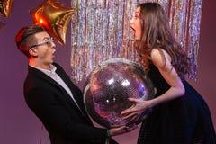 Pares jovenes sorprendentes atractivos que sostienen la bola de discoteca Fotografía de archivo libre de regalías
