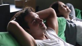 Pares jovenes tranquilos relajados que se relajan teniendo siesta en el sofá cómodo metrajes