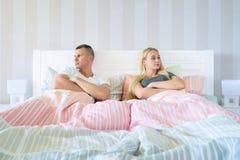 Pares jovenes trastornados que tienen problemas maritales o un desacuerdo que se sienta de lado a lado en la cama que hace frente fotografía de archivo libre de regalías