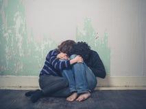 Pares jovenes tristes en piso fotografía de archivo libre de regalías