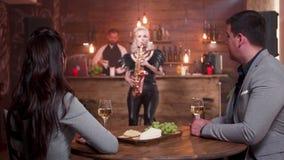 Pares jovenes una fecha romántica que escucha un músico de sexo femenino que juega en un saxofón almacen de video