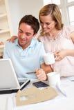 Pares jovenes usando de la tarjeta de crédito en el Internet Foto de archivo libre de regalías
