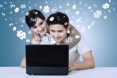 Pares jovenes usando el ordenador portátil con símbolos de moneda Fotos de archivo