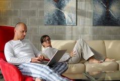Pares jovenes usando el ordenador portátil en casa Fotografía de archivo libre de regalías