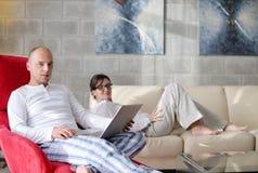 Pares jovenes usando el ordenador portátil en casa Imagen de archivo