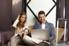 Pares jovenes usando el ordenador portátil en el pasillo del hotel Imagen de archivo