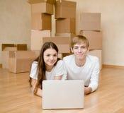 Pares jovenes usando el ordenador portátil en su nuevo hogar Fotos de archivo