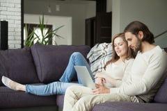 Pares jovenes usando el ordenador portátil que discute noticias o que hace shoppi en línea imágenes de archivo libres de regalías