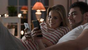 Pares jovenes usando el teléfono con Internet en dormitorio metrajes