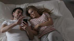Pares jovenes usando el teléfono con Internet en dormitorio almacen de video