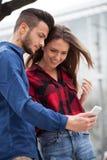 Pares jovenes usando el teléfono elegante Fotografía de archivo libre de regalías