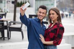 Pares jovenes usando el teléfono elegante Fotos de archivo libres de regalías