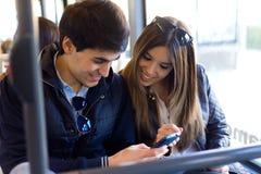Pares jovenes usando el teléfono móvil en el autobús Imagenes de archivo