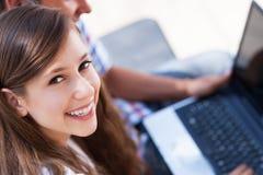 Pares jovenes usando la computadora portátil Imagenes de archivo
