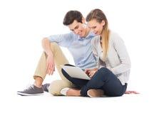 Pares jovenes usando la computadora portátil Imágenes de archivo libres de regalías
