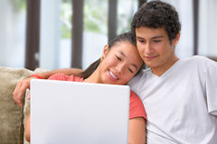 Pares jovenes usando la computadora portátil Fotos de archivo