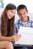 Pares jovenes usando la computadora portátil al aire libre Fotos de archivo libres de regalías
