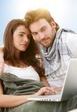Pares jovenes usando la computadora portátil al aire libre en luz del sol Imagen de archivo libre de regalías