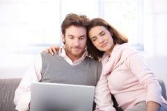Pares jovenes usando la computadora portátil en casa que sonríe Imagen de archivo
