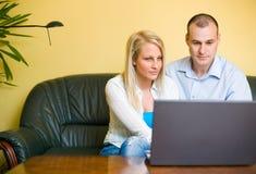 Pares jovenes usando la computadora portátil en el país. Fotografía de archivo libre de regalías