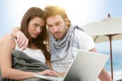 Pares jovenes usando la computadora portátil en la playa Foto de archivo libre de regalías