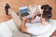 Pares jovenes usando la computadora portátil en sofá fotografía de archivo libre de regalías