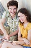 Pares jovenes usando la tableta digital Foto de archivo libre de regalías