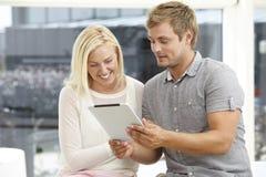 Pares jovenes usando la tableta digital Imágenes de archivo libres de regalías