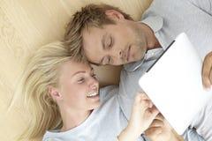 Pares jovenes usando la tableta digital Fotos de archivo
