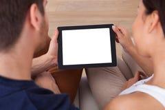 Pares jovenes usando la tableta digital junto Foto de archivo