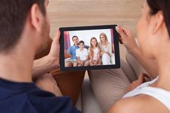 Pares jovenes usando la tableta digital junto Fotos de archivo