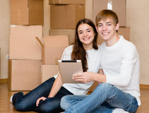 Pares jovenes usando la tableta en su nuevo hogar Imagen de archivo libre de regalías