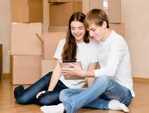 Pares jovenes usando la tableta en su nuevo hogar Fotos de archivo libres de regalías