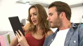 Pares jovenes usando la tableta para elegir día de fiesta metrajes