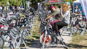 Pares jovenes usando las bicis inmóviles Imagenes de archivo