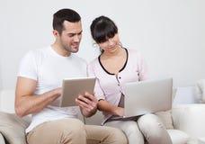 Pares jovenes usando las computadoras portátiles en sofá Foto de archivo libre de regalías