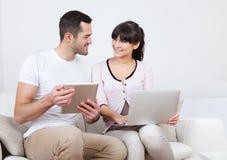 Pares jovenes usando las computadoras portátiles en sofá Fotos de archivo