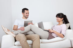 Pares jovenes usando las computadoras portátiles en sofá Fotos de archivo libres de regalías