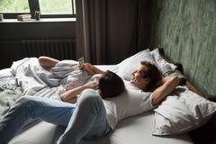 Pares jovenes usando los apps del teléfono móvil que se relajan en cama junto Imágenes de archivo libres de regalías