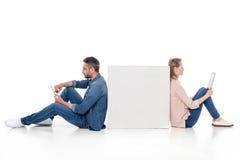 Pares jovenes usando los dispositivos digitales mientras que se sientan en el cubo blanco, Imagen de archivo libre de regalías