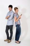 Pares jovenes usando los smartphones que se colocan aislados Fotos de archivo